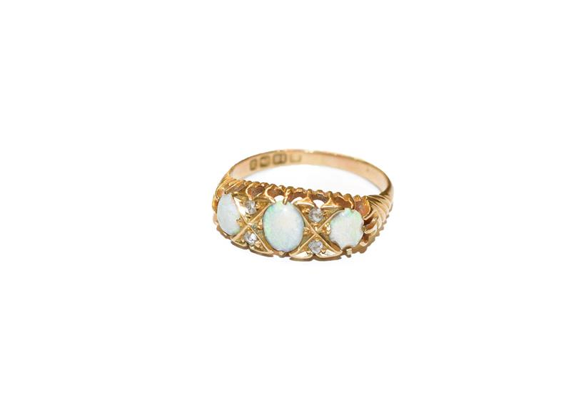 An 18 carat gold opal three stone ring, the graduated oval cabochon opals with rose cut diamond