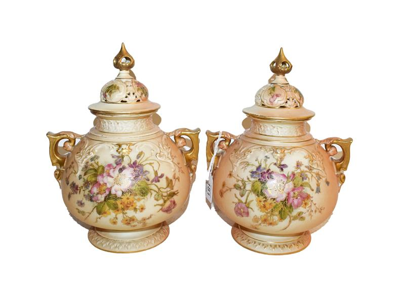 A matched pair of Royal Worcester vases and covers, c1917/1919 of ovoid form with scroll handles the