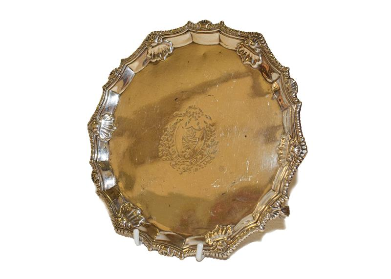 A George III silver waiter, by Ebenezer Coker, London, 1766, shaped circular and on three ball and