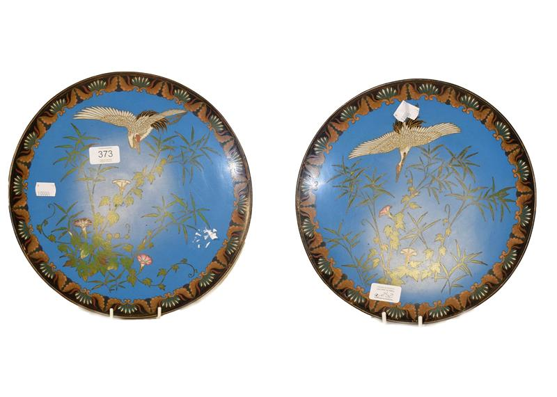 A pair of Japanese Meiji period cloisonne chargers, with blue ground decorated with cranes and