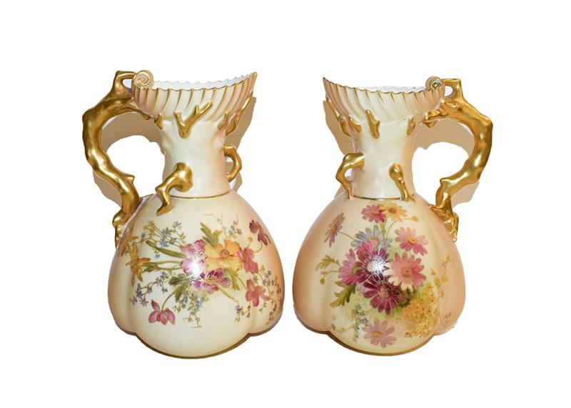 A pair of Royal Worcester ewers date code 1899, painted with flowers to a blush ground with gilt