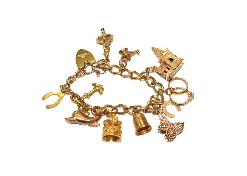 A 9 carat gold charm bracelet, hung with various charms including a thimble, a dolphin, a pram, a