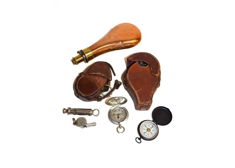 Two leather cased WWI compasses, two other small compasses, shot powder flask, and two whistles