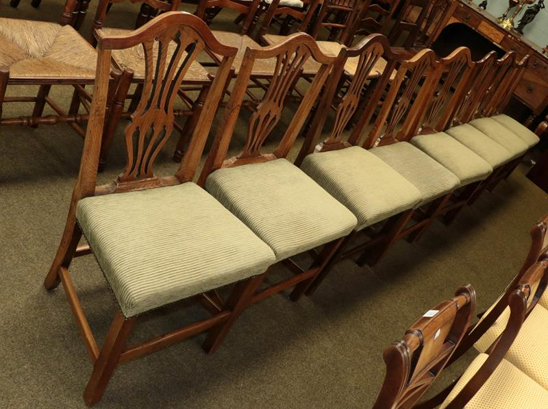 A set of eight Georgian oak Hepplewhite style dining chairs, recently re-upholstered (8)