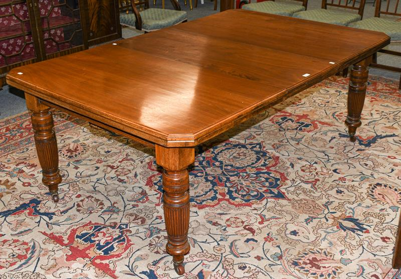 A Victorian walnut wind-out dining table with additional leaf, with canted corners, raised on turned