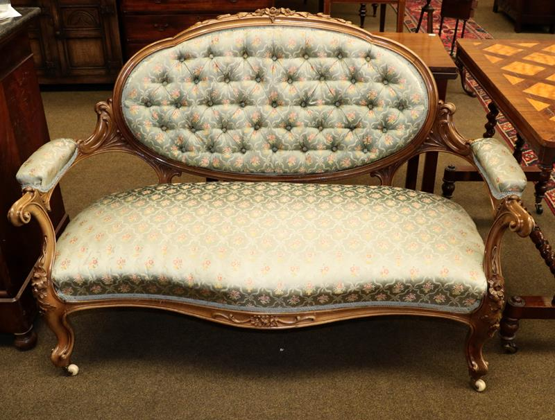 A Victorian carved walnut parlour sofa in the French taste with duck egg blue floral upholstery,