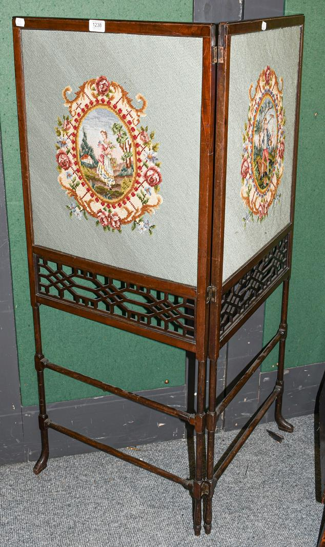 A Victorian mahogany two-fold screen with wool work panels and open fret carving, each section 114cm