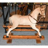 Early 20th century hide mounted rocking horse on pine trestle base, 102cm long by 98cm high to tip