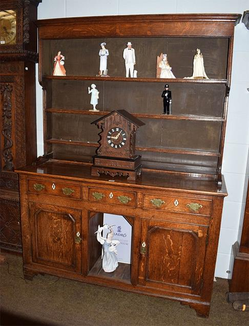 A George III oak dresser with plate rack, base with three drawers above central aperture and two