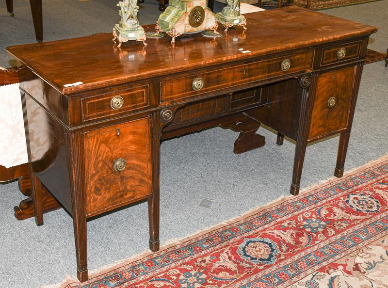 An early 19th century Neo-Classical mahogany sideboard incorporating two cellarets, with string