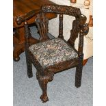 A 17th Century style carved oak corner chair with lion mask terminals, and acanthus carved