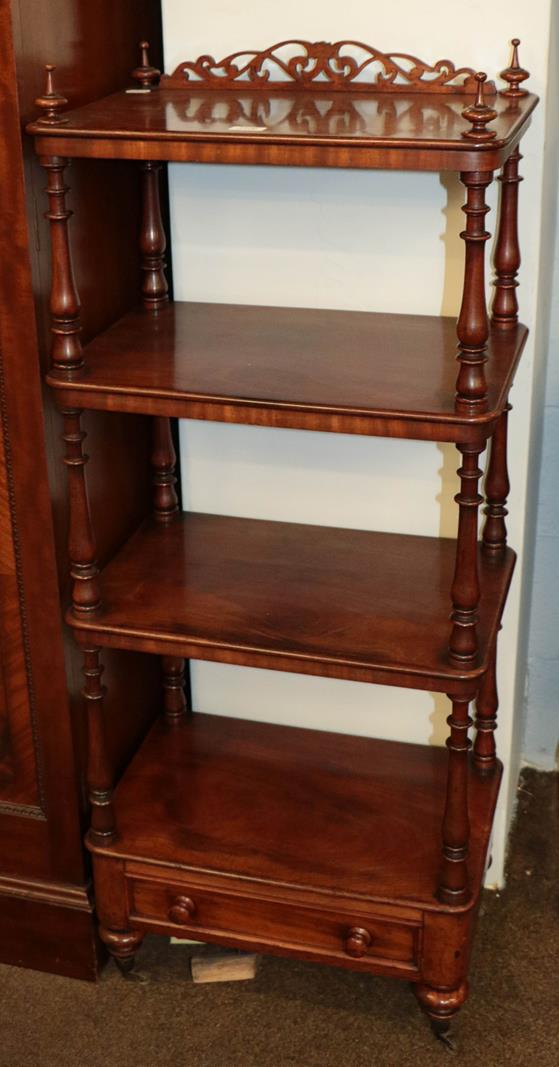A Victorian mahogany four-tier whatnot stand with fretwork pediment, turned supports and a single