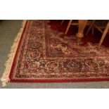 Machine made carpet of oriental design, the blood red field with central medallion framed by