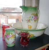 Two cranberry glass vases and a floral patterned jug and basin