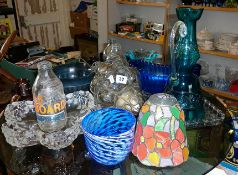 Collection of assorted coloured glassware including hall light shades, advertising milk bottles,