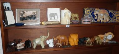 Two shelves of assorted elephant related ornaments and figures