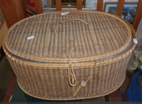 Oval lidded wicker basket with fitted interior