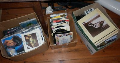 Two boxes of vinyl singles and another of cassette tapes