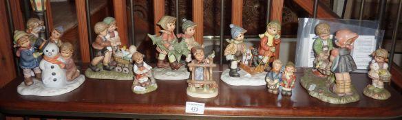 Shelf of Goebel Hummel children figurines and groups (10)