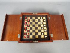 An Edwardian travelling chess set with diptych board and miniature bone pieces in natural and red