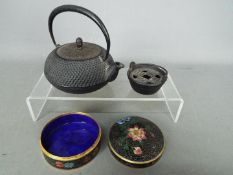 A cloisonné lidded trinket box of circular form, decorated with flowers against a black ground,