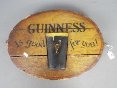An oval Guinness advertising sign, approximately 37 cm x 48 cm.