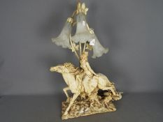 A decorative three stem table lamp in the form of a lady on horseback,