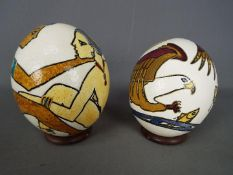 Two hand painted ostrich eggs with circular wooden stands.