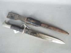 """A German dress bayonet with 9 3/4"""" blade with WKC makers mark, black composite grip, with scabbard."""
