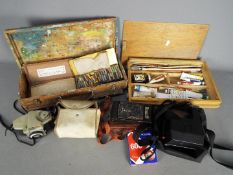 A collection of vintage artists equipment and cameras.