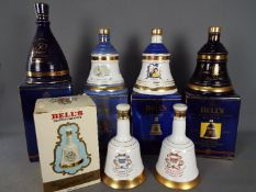 Six commemorative Bells ceramic whisky decanters (with contents) comprising four 70cl and two 50cl,