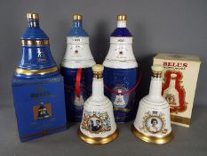 Five commemorative Bells ceramic whisky decanters (with contents) comprising four 75cl and one 70cl,