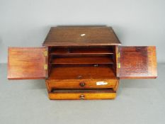 A desktop stationary cabinet having twin doors over three drawers,