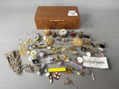 A copper box with contents including cufflinks, enamel badges, costume jewellery,