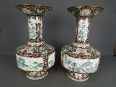 A large pair of Chinese enamel vases decorated to the body with panels of landscape scenes,