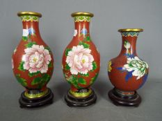 A pair of Chinese cloisonné vases decorated with flowers and birds and one similar,