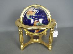 A gemstone terrestrial globe on brass stand, approximately 24 cm (h).