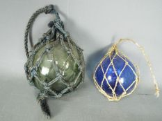 A vintage glass fisherman's float, approximately 13 cm (d) and one other of smaller proportion.