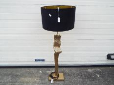 A good quality floor standing lamp with gold tone, bark effect finish and black shade,
