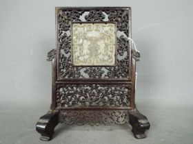 A carved wood and jade table screen,