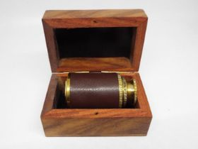 A brass and leather bound mini telescope,