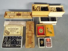 Lot to include vintage dominoes, playing cards, cribbage boards, chess pieces.