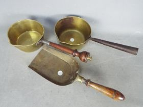 A vintage brass sauce pan with wooden handle and a brass sauce pan with brass shovel
