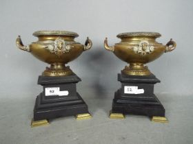 A pair of bronze urns raised on plinths (one plinth A/F), approximately 22 cm (h).