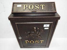 A modern black post box, horse and rider