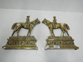 A pair of brass door stops in the form o