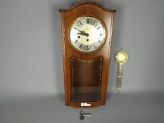 A late 20th century Rapport, Westminster chime, wall clock with key and pendulum,
