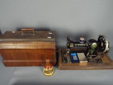 A wood cased Vibra sewing machine, a small Bells whisky decanter and contents, 18.