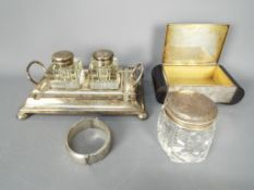 Lot to include an Art Deco silver plated cigarette box, plated ink well stand with two glass wells,