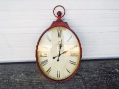 A large, antique style wall clock in the form of a pocket watch, approximately 97 cm x 46 cm.